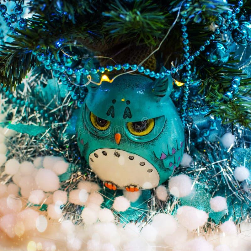 Μια θλιβερή τυρκουάζ κουκουβάγια κάθεται κάτω από ένα χριστουγεννιάτικο δέντρο που ντύνεται στις σφαίρες, γιρλάντες, tinsel, τεχν στοκ εικόνα