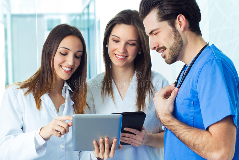 Μια ιατρική ομάδα που στέκεται στο διάδρομο νοσοκομείων στοκ εικόνες