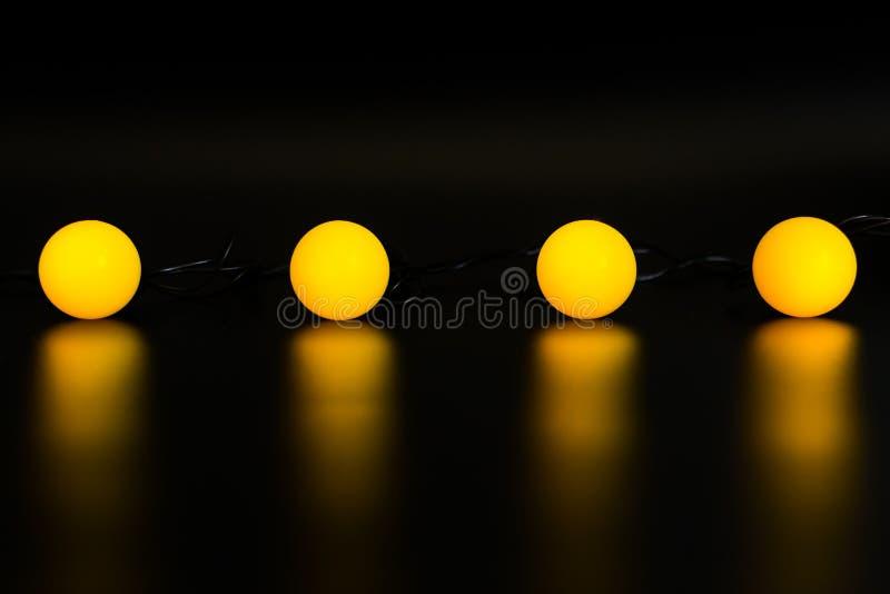 Μια κίτρινη globular γιρλάντα σε ένα μαύρο υπόβαθρο άνθρακα εκπέμπει το φως στοκ φωτογραφία με δικαίωμα ελεύθερης χρήσης