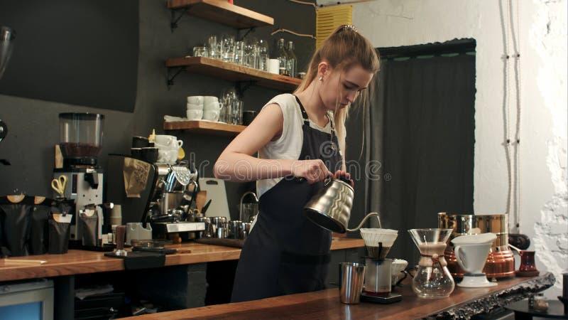 Μια κανάτα του νερού προσθέτει σε ένα επαγγελματικό φίλτρο για να κάνει ένα παραδοσιακό καυτό εκχύλισμα καφέ σε ένα φίλτρο στην α στοκ εικόνα