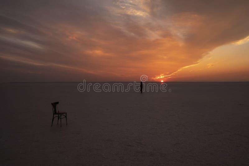 Μια καρέκλα και ένα κορίτσι στην αλατισμένη λίμνη στοκ εικόνες