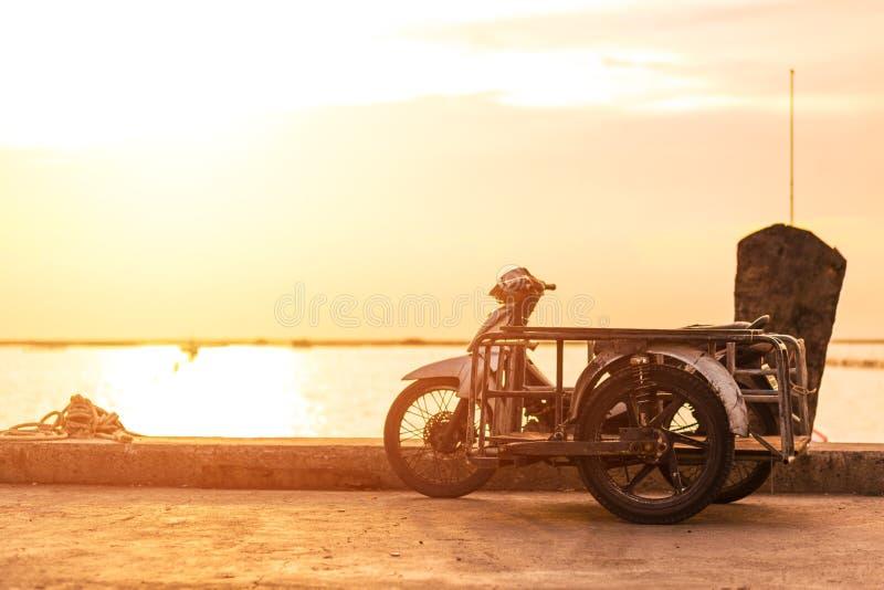 Μια καρότσα motorcicle κοντά στη θάλασσα με το ηλιοβασίλεμα στοκ φωτογραφίες