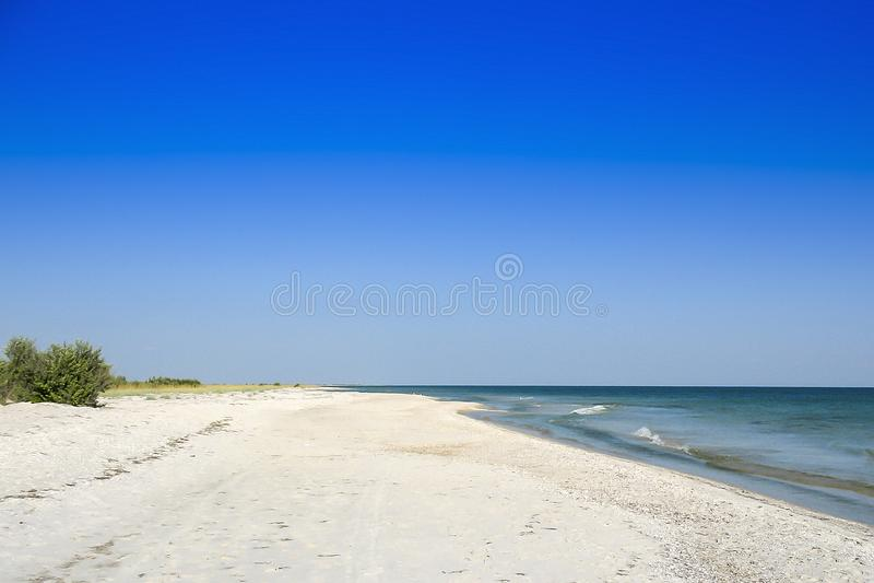 Μια καυτή ασυννέφιαστη ημέρα τα κύματα κύλησαν στην ξηρά την αμμώδη παραλία στοκ φωτογραφίες