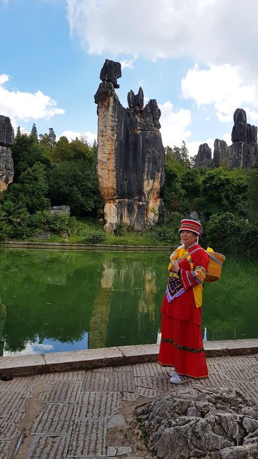 Μια κινεζική κυρία στο παραδοσιακό φόρεμα μπροστά από το θαυμάσιο τοπίο του πέτρινου δάσους ή του Shilin στοκ φωτογραφίες με δικαίωμα ελεύθερης χρήσης