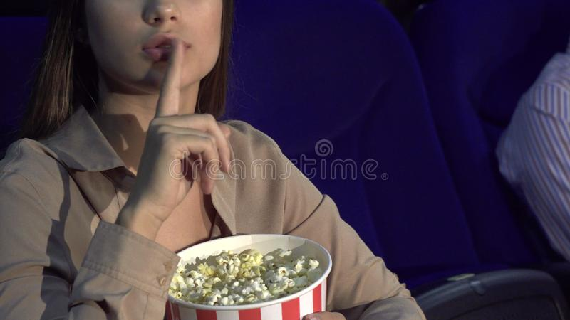 Μια κινηματογράφηση σε πρώτο πλάνο για το πώς ένα κορίτσι τρώει popcorn και παρουσιάζει ένα σημάδι της σιωπής στοκ εικόνα με δικαίωμα ελεύθερης χρήσης