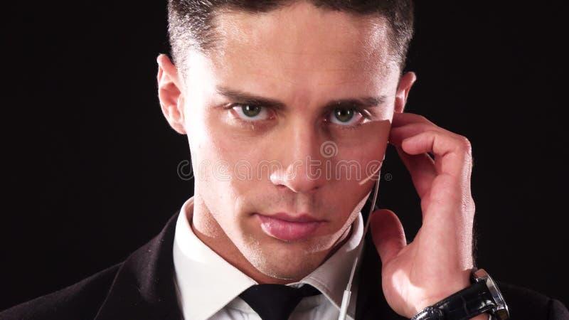Μια κινηματογράφηση σε πρώτο πλάνο του προσώπου ενός τύπου που με ένα σοβαρό πρόσωπο ακούει το ειδικό ακουστικό του στοκ εικόνες