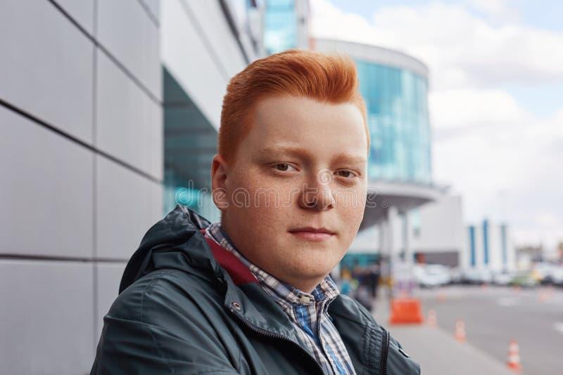 Μια κινηματογράφηση σε πρώτο πλάνο ενός όμορφου φακιδοπρόσωπου redhead αγοριού που στέκεται λοξά το μοντέρνο σακάκι που έχει το β στοκ εικόνα με δικαίωμα ελεύθερης χρήσης