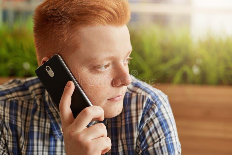 Μια κινηματογράφηση σε πρώτο πλάνο του μοντέρνου redhead ατόμου με τις φακίδες και τα σκοτεινά μάτια που κάθεται λοξά πέρα από το στοκ εικόνα