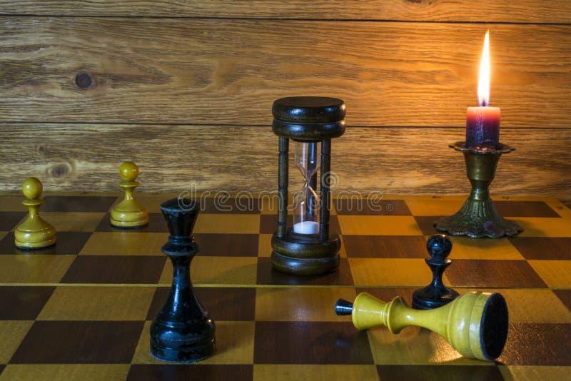 Μια κλεψύδρα, ένα καίγοντας κερί και κομμάτια σκακιού που στέκονται σε έναν πίνακα σκακιού στοκ εικόνες