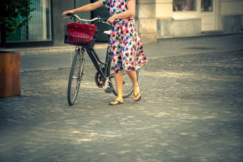Μια κομψή γυναίκα σε ένα όμορφο ζωηρόχρωμο φόρεμα περπατά στις οδούς με ένα ποδήλατο το καλοκαίρι στοκ φωτογραφία με δικαίωμα ελεύθερης χρήσης