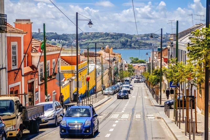 Μια κυκλοφορία της οδού κλίσεων στη Λισσαβώνα με τα ζωηρόχρωμα κτήρια κατά μήκος της άκρης του δρόμου και μιας άποψης θάλασσας στοκ φωτογραφία