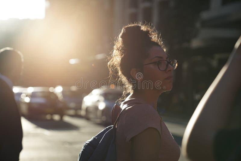 Μια κυρία τουριστών ήταν έτοιμη να διασχίσει το δρόμο στην πόλη μέσα μετά από την εργασία στοκ φωτογραφίες