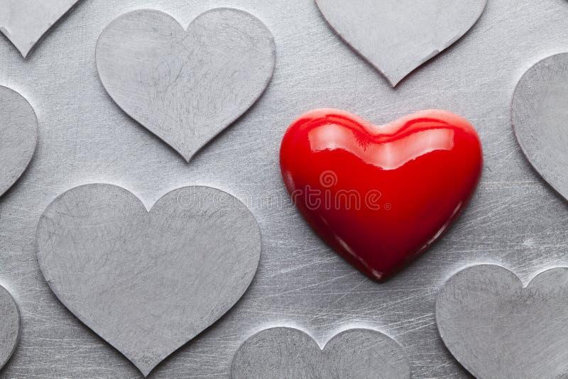 Μια κόκκινες καρδιά και ομάδα ασημένιων καρδιών στοκ εικόνα με δικαίωμα ελεύθερης χρήσης