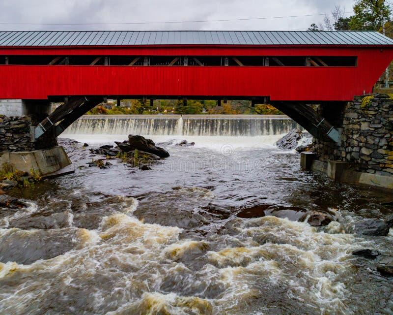 Μια κόκκινη καλυμμένη γέφυρα που χτίζεται πρώτα το 1883 εκτείνεται μια γρήγορα ροή στοκ φωτογραφίες