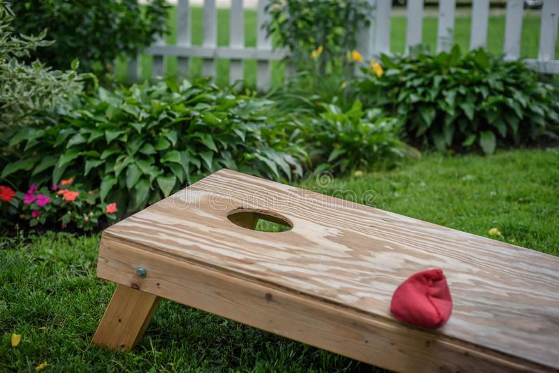 μια κόκκινη τσάντα στον ξύλινο πίνακα παιχνιδιών τρυπών καλαμποκιού hommade στοκ εικόνα με δικαίωμα ελεύθερης χρήσης