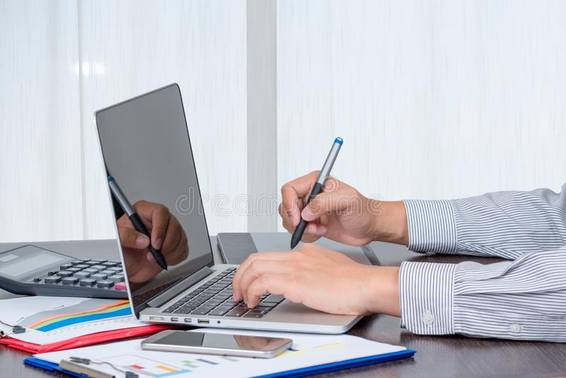 Μια λαβή επιχειρηματιών άγγιξε τη μάνδρα για να ελέγξει τα στοιχεία της έκθεσης όγκου πώλησης στοκ εικόνες