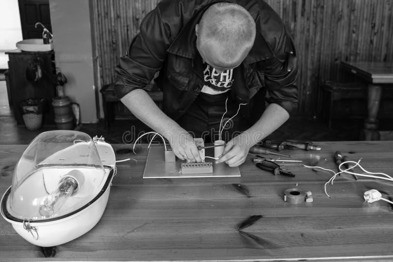 Μια λειτουργώντας εργασία ηλεκτρολόγων ατόμων, συλλέγει το ηλεκτρικό κύκλωμα ενός μεγάλου άσπρου λαμπτήρα οδών με τα καλώδια, ένα στοκ εικόνες με δικαίωμα ελεύθερης χρήσης