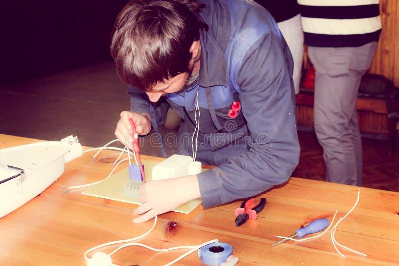 Μια λειτουργώντας εργασία ηλεκτρολόγων ατόμων, συλλέγει το ηλεκτρικό κύκλωμα ενός μεγάλου άσπρου λαμπτήρα οδών με τα καλώδια, ένα στοκ εικόνες