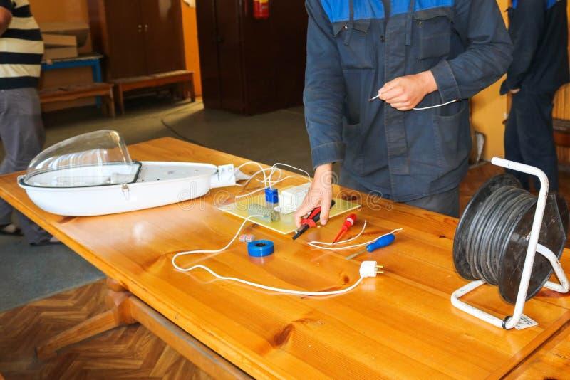 Μια λειτουργώντας εργασία ηλεκτρολόγων ατόμων, συλλέγει το ηλεκτρικό κύκλωμα ενός μεγάλου άσπρου λαμπτήρα οδών με τα καλώδια, ένα στοκ φωτογραφία με δικαίωμα ελεύθερης χρήσης