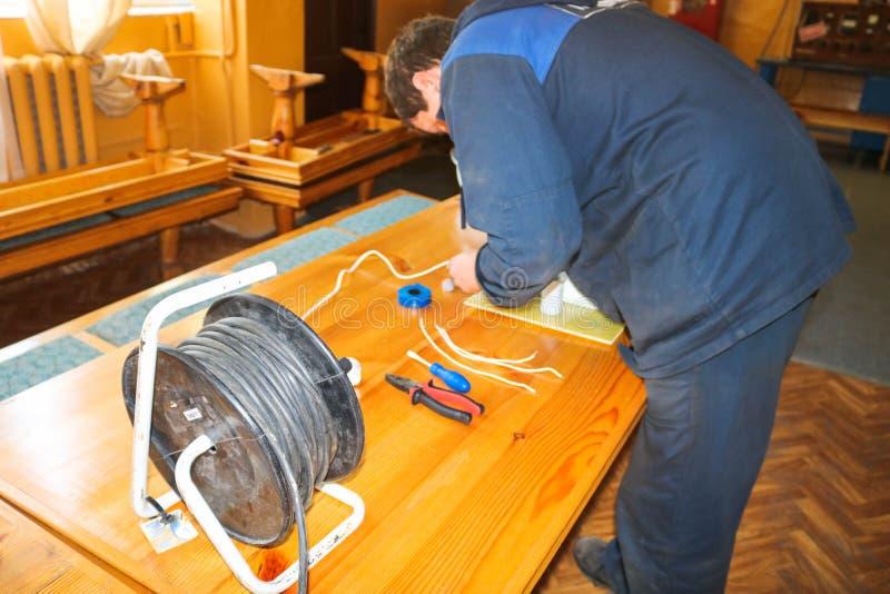 Μια λειτουργώντας εργασία ηλεκτρολόγων ατόμων, συλλέγει το ηλεκτρικό κύκλωμα ενός μεγάλου άσπρου λαμπτήρα οδών με τα καλώδια, ένα στοκ φωτογραφίες με δικαίωμα ελεύθερης χρήσης
