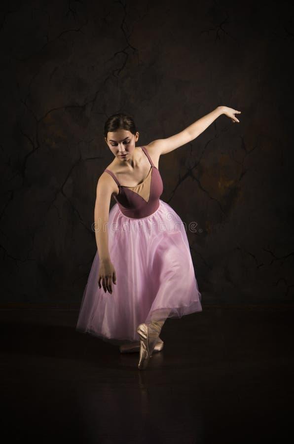 Μια λεπτή κοπέλα με ροζ φούστα και μπεζ μπαλέτο χορού στοκ φωτογραφίες