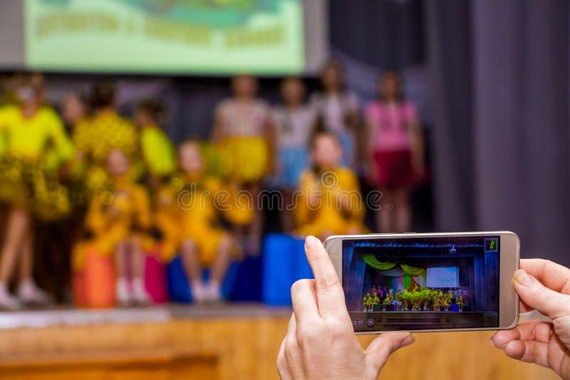 Μια μαγνητοσκόπηση γυναικών ένα βίντεο που χρησιμοποιεί ένα smartphone σε μια αίθουσα συναυλιών κατά τη διάρκεια παιδιών performa στοκ εικόνα με δικαίωμα ελεύθερης χρήσης