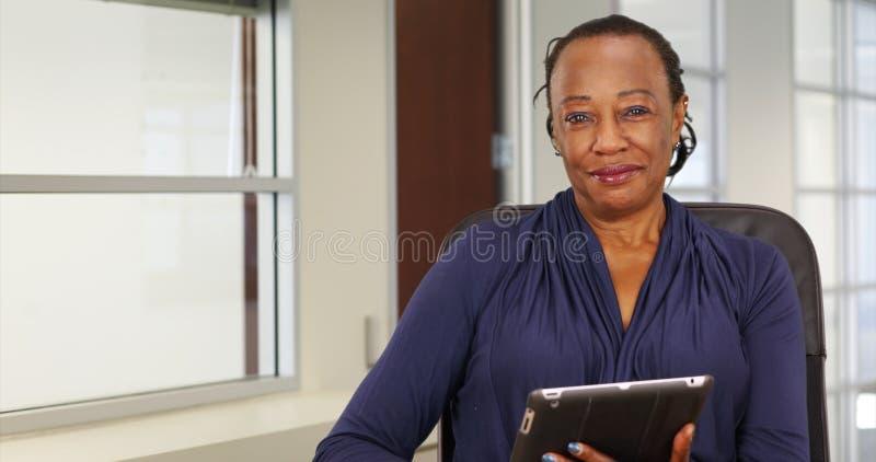 Μια μαύρη επιχειρηματίας χρησιμοποιεί ευτυχώς την ταμπλέτα της θέτοντας για ένα πορτρέτο στοκ εικόνες