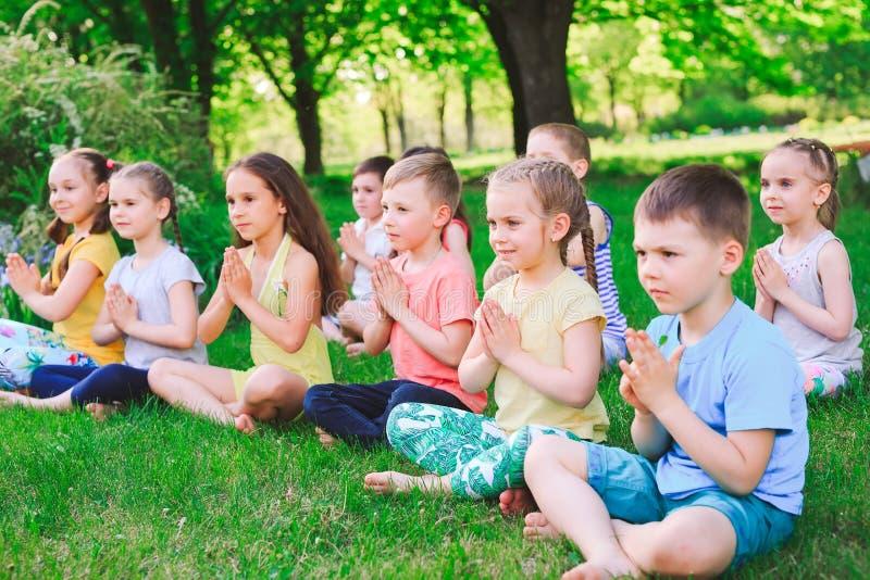 Μια μεγάλη ομάδα παιδιών συμμετείχε στη γιόγκα στη συνεδρίαση πάρκων στη χλόη στοκ εικόνα με δικαίωμα ελεύθερης χρήσης