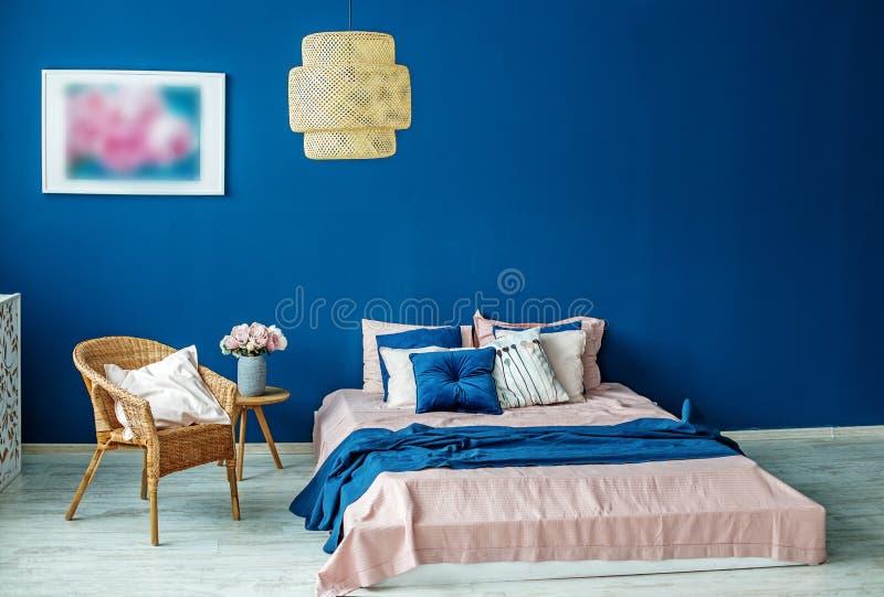 Μια μεγάλη ψάθινη σκιά κρεμά πέρα από το κρεβάτι Εσωτερικό έννοιας, δωμάτιο, στοκ εικόνες
