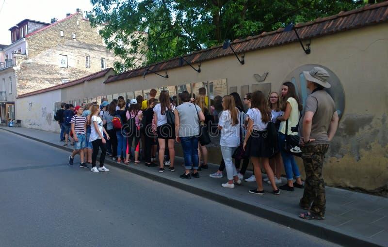 Μια μεγάλη ομάδα τουρίστας-σπουδαστών δίπλα στο διάσημο σύνταγμα του Uzupis στοκ φωτογραφίες
