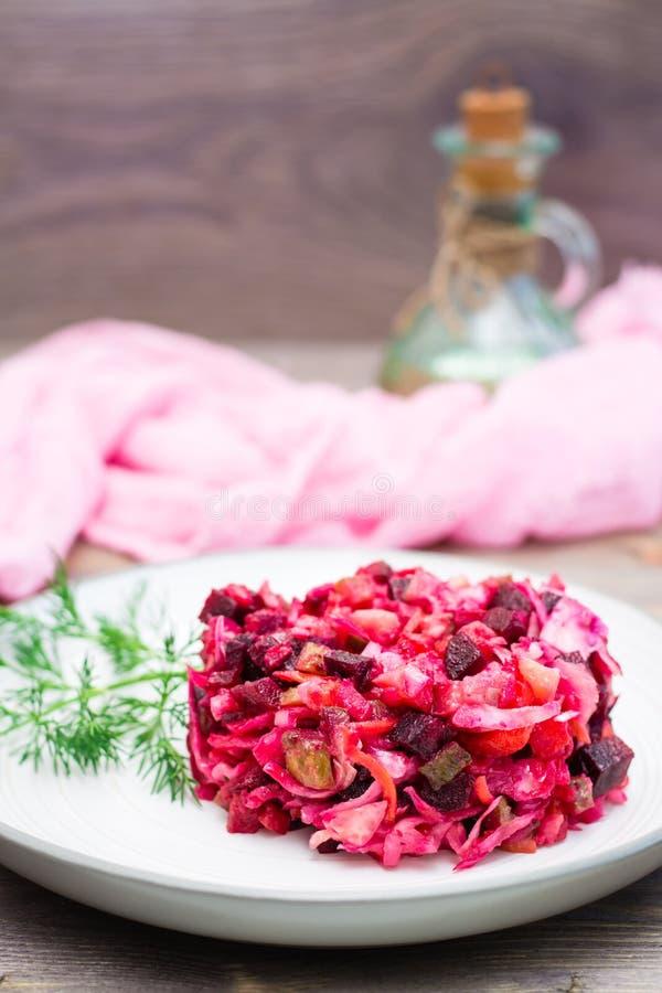 Μια μερίδα του vinaigrette - μια σαλάτα των βρασμένων λαχανικών, sauerkraut και των παστωμένων αγγουριών σε ένα πιάτο σε έναν ξύλ στοκ εικόνες