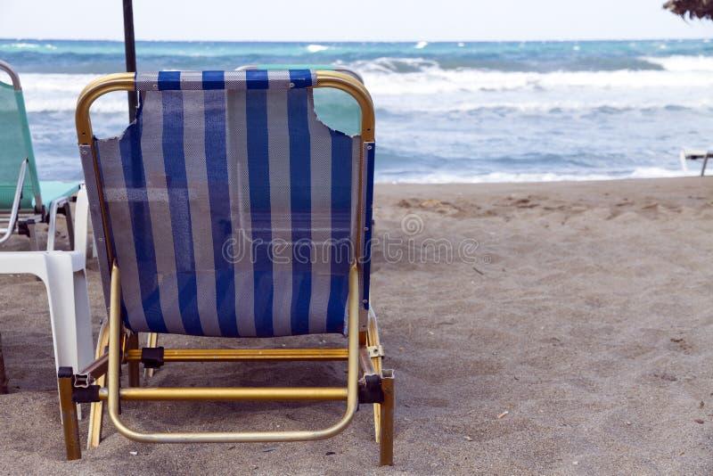 Μια μεταλλική καρέκλα σε μια αμμώδη παραλία με το υψηλό κύμα, Κρήτη, Ελλάδα στοκ φωτογραφία με δικαίωμα ελεύθερης χρήσης