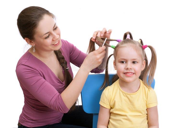 Μια μητέρα την κάνει λίγη κόρη ένα όμορφο hairstyle στοκ εικόνα