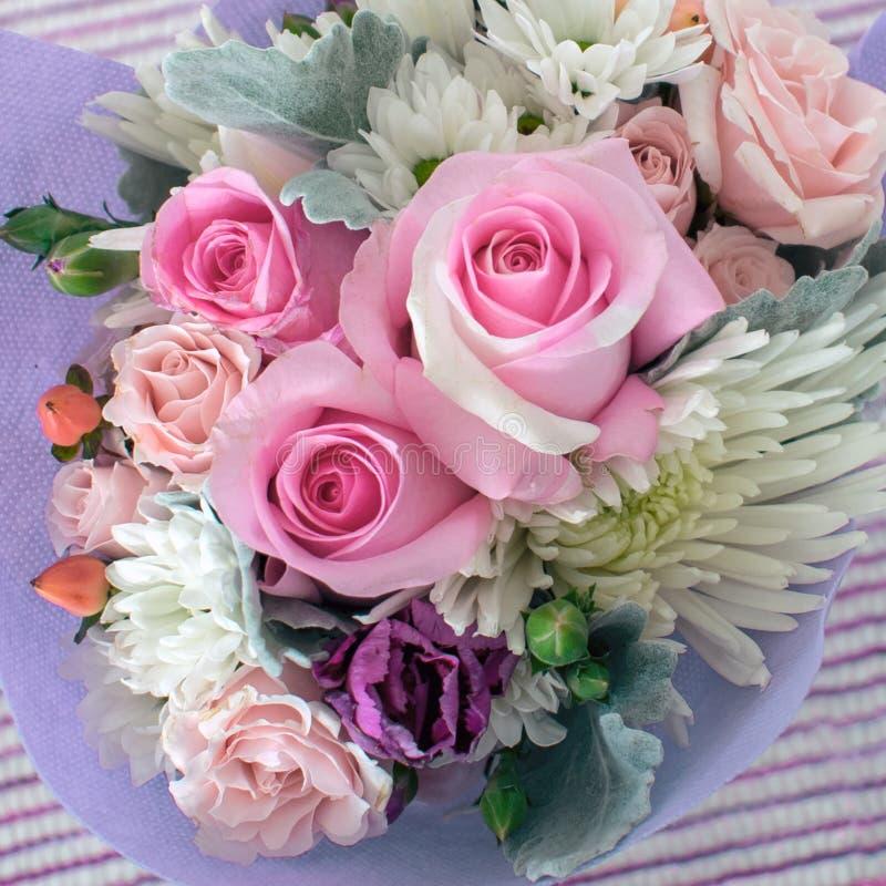 Μια μικρή ανθοδέσμη των λεπτοκαμωμένων λουλουδιών συμπεριλαμβανομένων των ρόδινων τριαντάφυλλων στοκ εικόνα