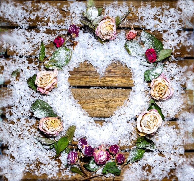 Μια μικρή καρδιά που σχεδιάζεται του χιονιού σε έναν ξύλινο πίνακα στοκ εικόνα