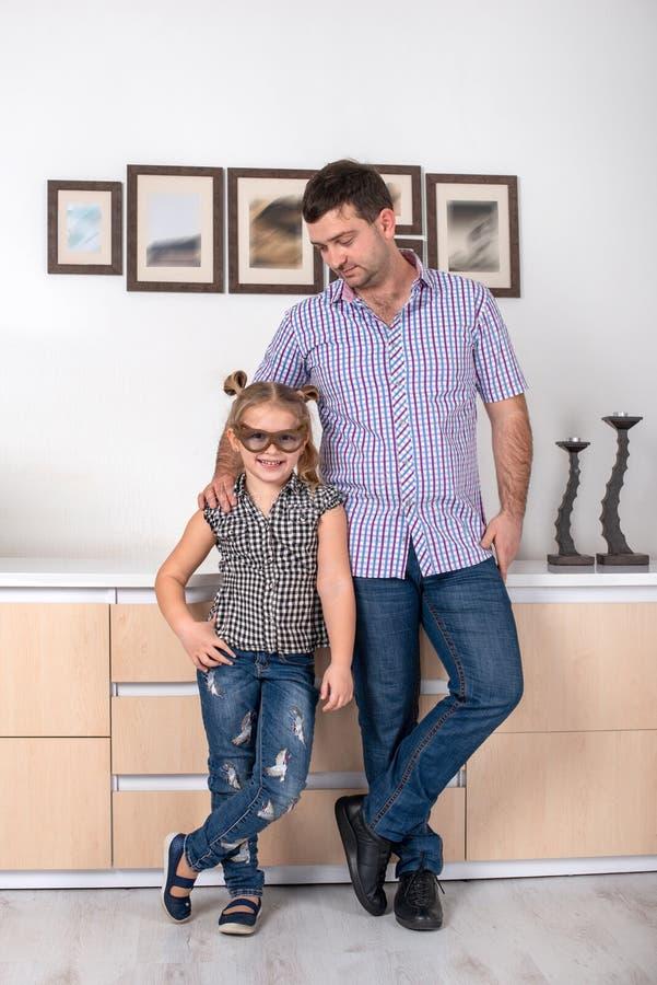 Μια μικρή κόρη με τα γυαλιά αστείου και ο μπαμπάς που στέκεται στο δωμάτιο στο ίδιο πράγμα θέτουν στοκ εικόνα με δικαίωμα ελεύθερης χρήσης