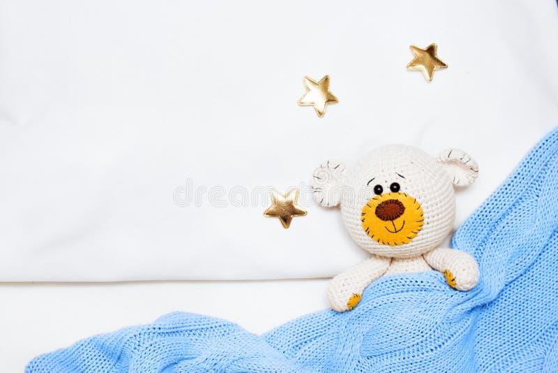 Μια μικρή πλεκτή παιχνίδι-αρκούδα μωρών amigurumi καλύπτεται με ένα μπλε κάλυμμα, βάλτε οριζόντια, τοπ άποψη στοκ φωτογραφία