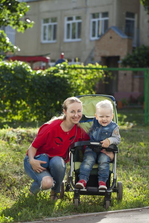 Μια μικρή συνεδρίαση αγοριών σε μια αναπηρική καρέκλα και περπάτημα με τη μητέρα του στοκ εικόνα με δικαίωμα ελεύθερης χρήσης