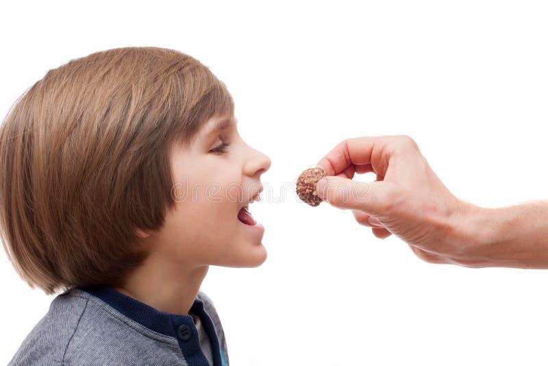 Μια μικρή σφαίρα σοκολάτας δαγκωμάτων αγοριών από το χέρι ατόμων στοκ εικόνες με δικαίωμα ελεύθερης χρήσης