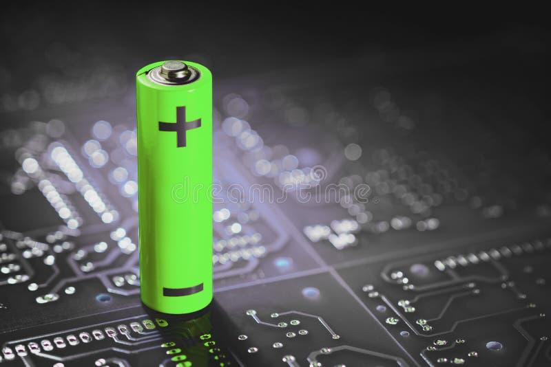 Μια μπαταρία ιόντων λιθίου στέκεται στο φόντο των πλακετών ηλεκτρονικών κυκλωμάτων στοκ φωτογραφίες