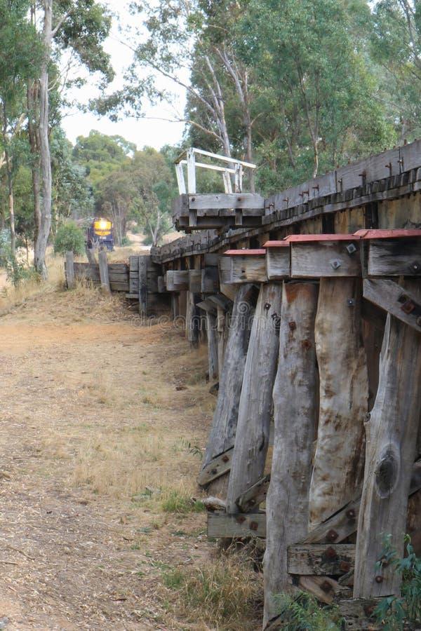 Μια μπλε και χρυσή μηχανή diesel κατηγορίας σιδηροδρόμων Υ κληρονομιάς βικτοριανή πλησιάζει την ξύλινη γέφυρα τρίποδων κοντά sta  στοκ φωτογραφία με δικαίωμα ελεύθερης χρήσης