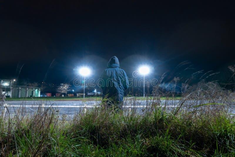 Μια μυστηριώδης οπλισμένη φιγούρα, με πίσω στην κάμερα Κοιτάζοντας έξω σε μια βιομηχανική περιοχή και φώτα στο δρόμο τη νύχτα του στοκ φωτογραφίες