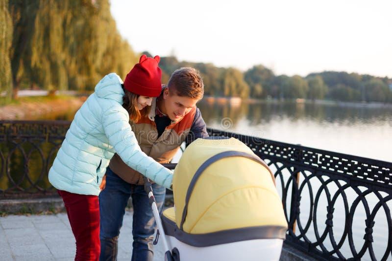 Μια νέα αγαπώντας οικογένεια περπατά από τη λίμνη με έναν περιπατητή Το χαμογελώντας ζεύγος γονέων με το καροτσάκι μωρών στο πάρκ στοκ εικόνες