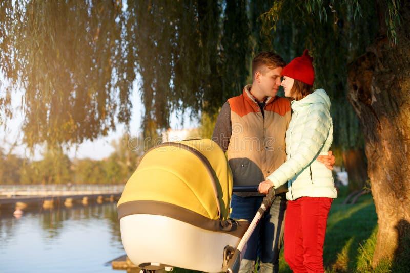 Μια νέα αγαπώντας οικογένεια περπατά από τη λίμνη με έναν περιπατητή Χαμογελώντας ζεύγος γονέων με το καροτσάκι μωρών στο πάρκο φ στοκ εικόνες