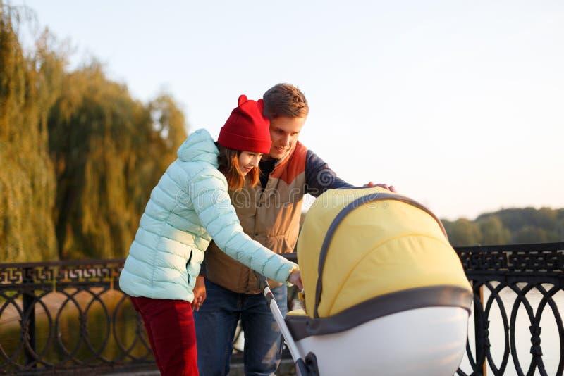 Μια νέα αγαπώντας οικογένεια περπατά από τη λίμνη με έναν περιπατητή Το χαμογελώντας ζεύγος γονέων με το καροτσάκι μωρών στο πάρκ στοκ εικόνες με δικαίωμα ελεύθερης χρήσης