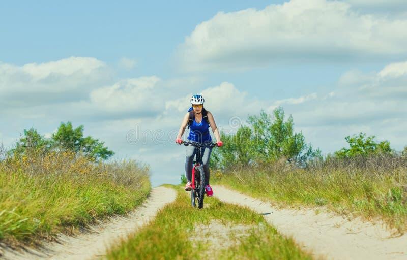 Μια νέα γυναίκα - ένας αθλητής σε ένα κράνος που οδηγά ένα ποδήλατο βουνών έξω από την πόλη στοκ εικόνες