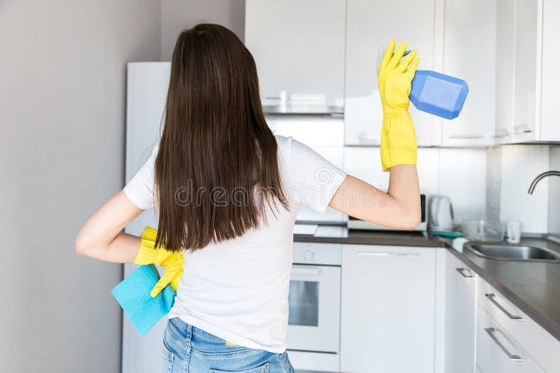 Μια νέα γυναίκα από μια επαγγελματική καθαρίζοντας επιχείρηση καθαρίζει στο σπίτι Ένα άτομο πλένει την κουζίνα στα κίτρινα γάντια στοκ εικόνες