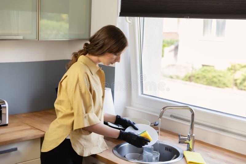 Μια νέα γυναίκα καθαρίζει στην κουζίνα, που πλένει τα πιάτα στοκ φωτογραφία