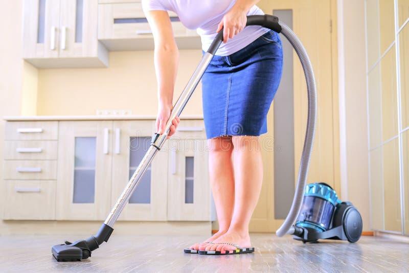 Μια νέα γυναίκα καθαρίζει το διαμέρισμα Στα χέρια μιας οικιακής συσκευής, ηλεκτρική σκούπα r στοκ φωτογραφία