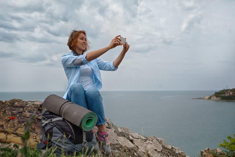 Μια νέα γυναίκα κατάκτησε την κορυφή βουνών και αποφάσισε να πάρει μια εικόνα μιας όμορφης πανοραμικής άποψης στοκ εικόνες